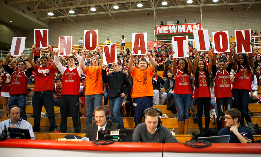 Basketball fans at the 2014 Zero Landfill Game hold up an 'innovation' sign.