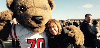 Cornell mascot bear Touchdown stands with their paw around a woman