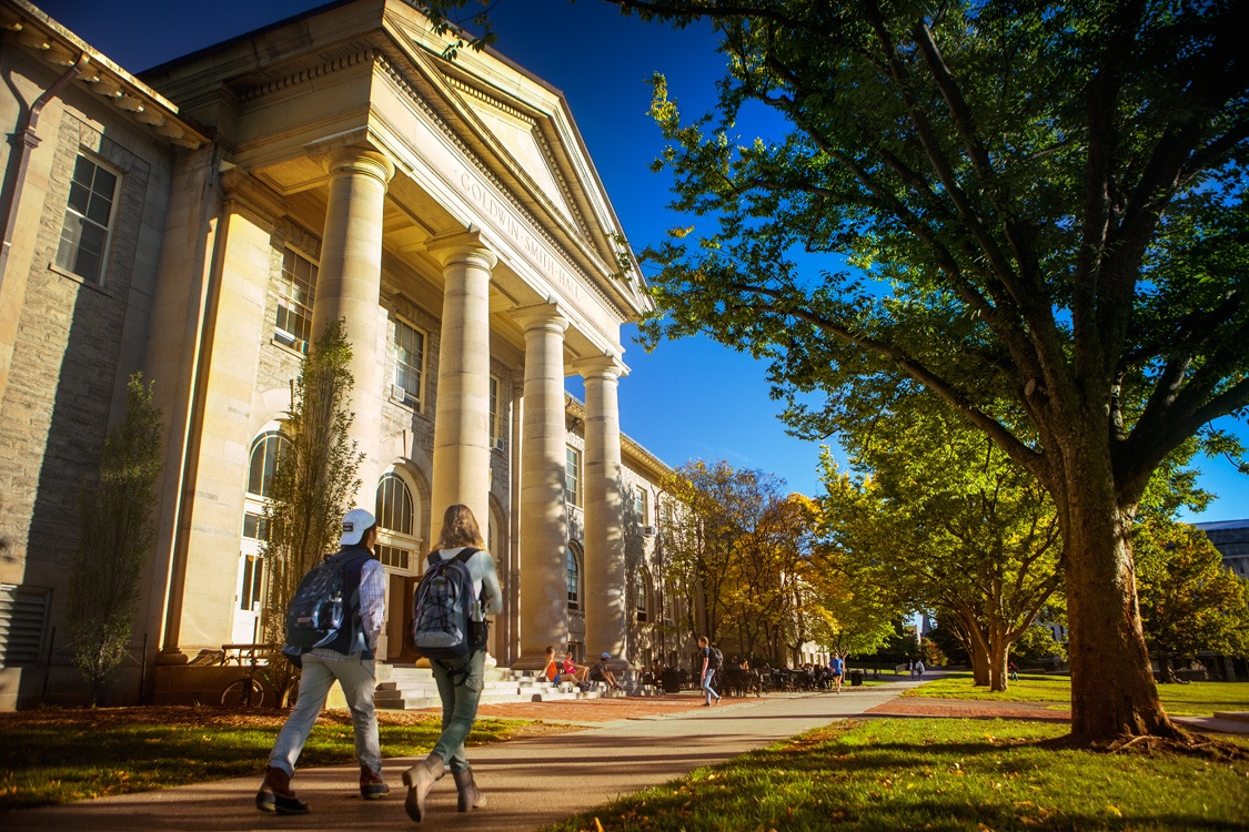 Students walk past Goldwin Smith Hall in fall.
