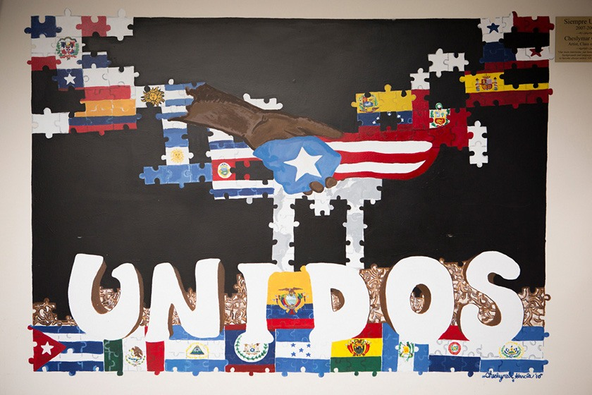 "A painting of a handshake and the word ""Unidos"" decorating the Latino Living Center"