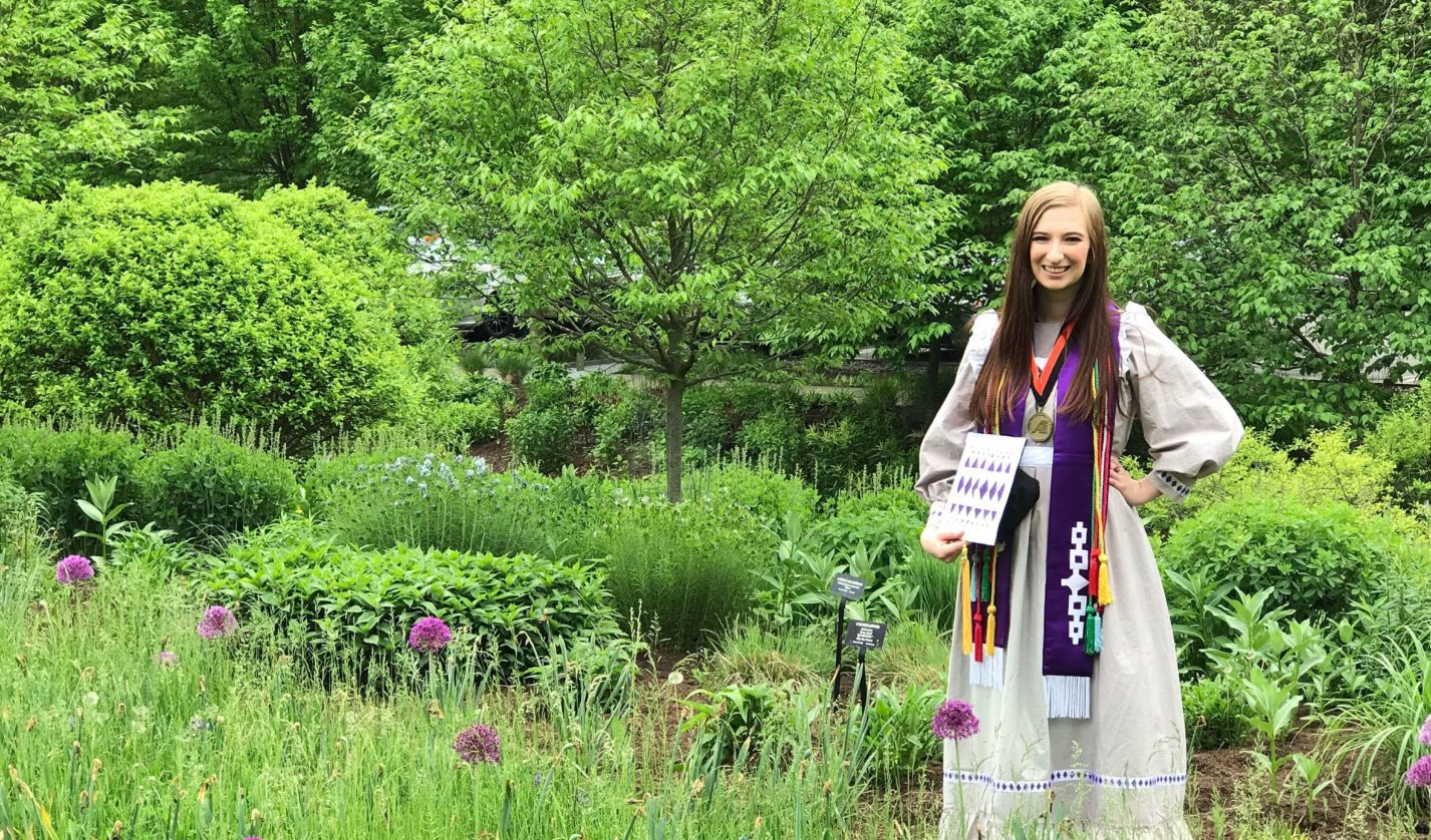 Bailee Hopkins-Hensley celebrating her undergraduate graduation in the Cornell Botanic Gardens, wearing traditional Choctaw regalia she made herself.