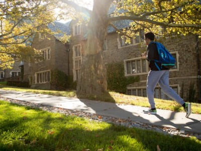 Cornell student with backpack walks on campus sidewalk