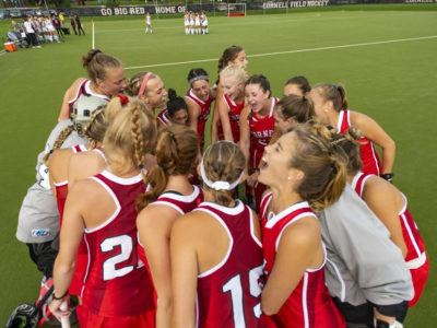 Women's field hockey team huddling on the field