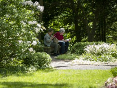 Two older adults sit together on a bench