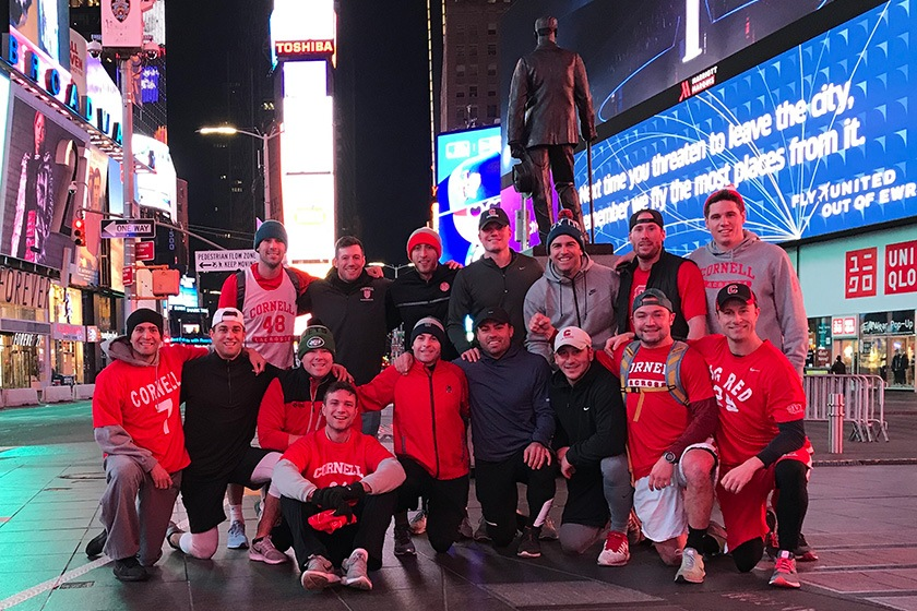 Sixteen lacrosse alumni wearing Cornell gear with Times Square in the background