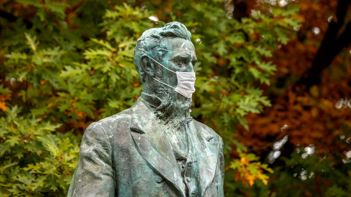 The statue of Ezra Cornell wearing a mask.